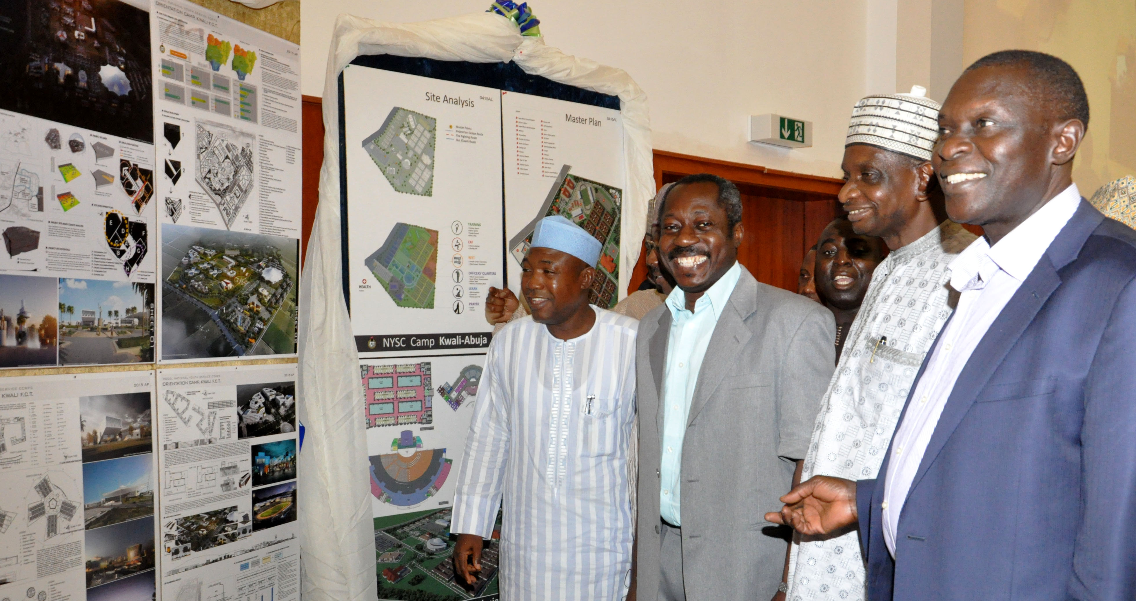 PIC. 9. FROM LEFT: DIRECTOR OF PROCUREMENT, FCDA, ALHAJI ADEWALE DAMBTA; DEPUTY DIRECTOR, ARCHITECTURE, PUBLIC BUILDING DEPARTMENT, MR ADEBOWALE ADEMO; DIRECTOR, SATELLITE TOWN DEVELOPMENT, MR SOSO MOHAMMED AND DIRECTOR, PUBLIC BUILDING, MR BERNARD LOT, ADMIRING THE MASTER PLAN CONCEPT OF THE WINNING ENTRY OF THE ARCHITECTURAL DESIGN COMPETITION FOR THE MODEL NYSC ORIENTATION CAMP, KWALI IN ABUJA ON WEDNESDAY (8/4/15). 1850/8/4/2015/OTU/CH/BJO/NAN