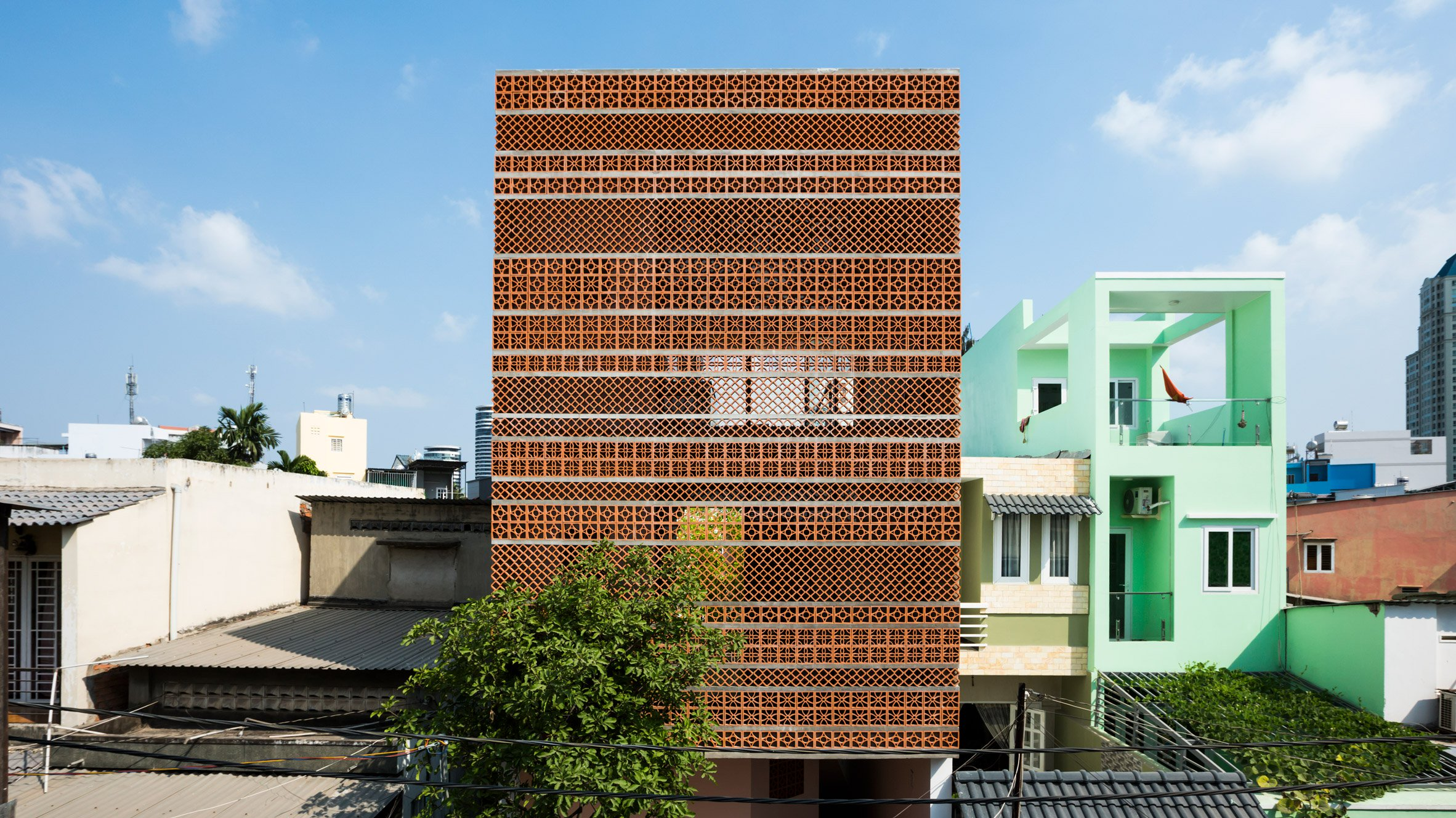 A terracotta facade and green pockets make this apartment for Modern house hanoi